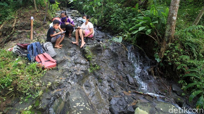 Sejumlah siswa/i SD Kanisius Kenalan berjalan menyusuri hutan dan aliran sungai saat melaksanakan program pembelajaran luar ruangan dengan nama Tilik Belik di kawasan pegunungan Menoreh, Duren Sawit, Kulonprogo, Yogyakarta, Sabtu (20/3/2021).