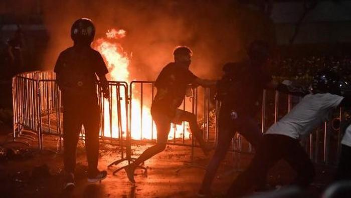 Pengunjuk rasa pro-demokrasi mencoba untuk menghapus pagar barikade di samping api dari bom molotov yang dilemparkan selama bentrokan dengan polisi anti huru hara pada demonstrasi anti-pemerintah di Bangkok pada 20 Maret 2021. (Lillian Suwan/AFP)