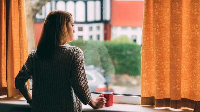 Woman staying home for safety during coronavirus pandemic and observing empty city