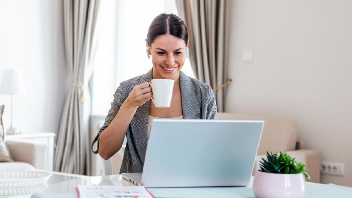 Business Women at home during pandemic isolation working on laptop and drinking coffee.Image of young pleased happy cheerful cute beautiful business woman sit indoors in office using laptop computer