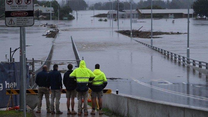People stand on the banks of the Nepean River at Jamisontown on the western outskirts of Sydney Monday, March 22, 2021. Australia's most populous state of New South Wales has issued more evacuation orders following the worst flooding in decades. (AP Photo/Mark Baker)