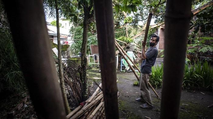 Agus Hartadi (tengah) berpose dengan memegang tas hasil kerajinannya di Desa Loyok, Sakra, Lombok Timur, Nusa Tenggara Barat.