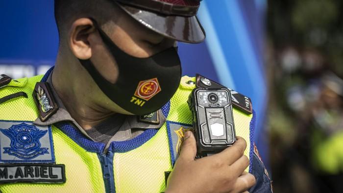 Kapolda Metro Jaya Irjen Pol Fadil Imran (kanan) didampingi Wakapolda Metro Jaya Brigjen Pol Hendro Pandowo (ketiga kanan) dan Dirlantas Polda Metro Jaya Kombes Pol Sambodo (kedua kanan) menunjukkan kepada media petugas Polisi Lalu Lintas yang telah dilengkapi dengan kamera Electric Traffic Law Enforcement (ETLE)  Mobil saat peluncuran di Polda Metro Jaya, Sabtu (20/3/2021). Polda Metro Jaya meluncurkan 30 perangkat kamera ETLE Mobile yang terpasang di badan petugas (body cam), helm (helmet cam), dan dashboard mobil (dash cam). ANTARA FOTO/Aprillio Akbar/hp.