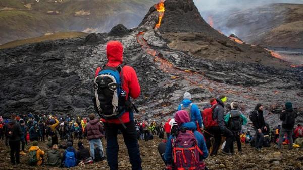 Wisatawan berdatangan menyaksikan aliran lahar panas di lereng gunung Fahradaslfjall. Bahkan ada yang menerbangkan drone dengan ketinggian beberapa meter di atas lava. (AFP)