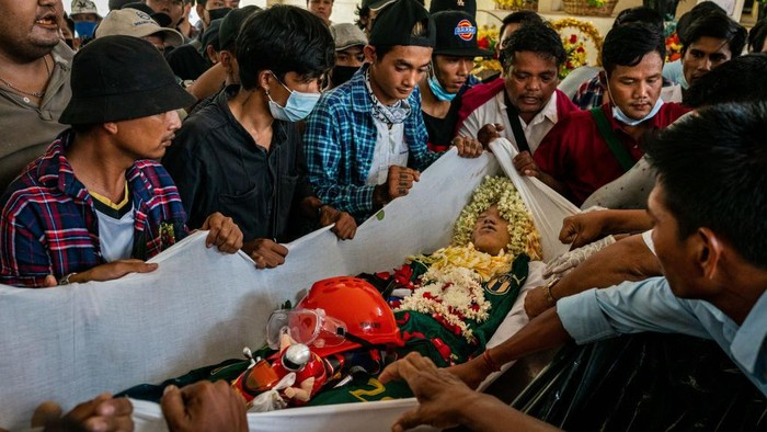 YANGON, MYANMAR - MARCH 21: (EDITORS NOTE: Image contains graphic content) Mourners prepare to carry the body of Aung Kaung Htet, 15, who was killed when military junta forces opened fire on anti-coup protesters, in a coffin during his funeral on March 21, 2021 in Yangon, Myanmar. Myanmars military Junta charged deposed de-facto leader Aung San Suu Kyi with accepting bribes and taking illegal payments in gold, as it also continued a brutal crackdown on a nationwide civil disobedience movement in which thousands of people have turned out in continued defiance of tear gas, rubber bullets and live ammunition. Over 180 people have been killed so far according to the U.N. (Photo by Stringer/Getty Images)