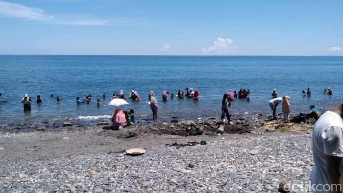 Warga mencari butiran emas di Pantai Pohon Batu, Maluku Tengah.
