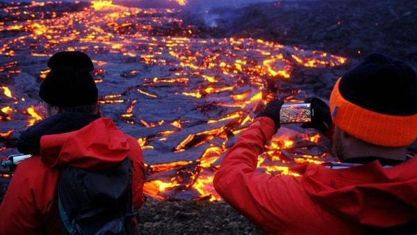 Wisatawan mengabadikan lava panas dalam jepretan kamera. (Getty Images)