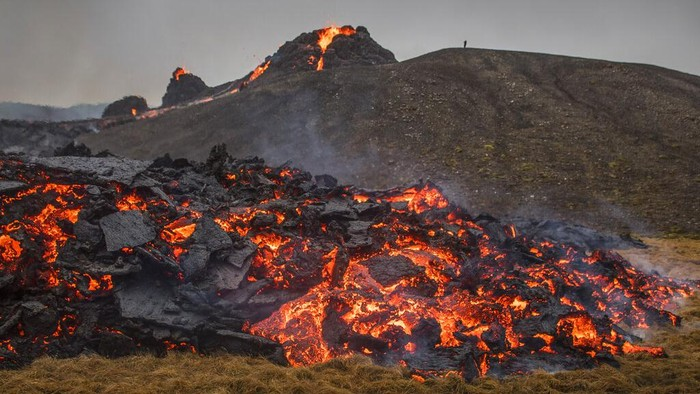 Lava flows from an eruption of a volcano on the Reykjanes Peninsula in southwestern Iceland on Saturday, March 20, 2021. The eruption of the long-dormant volcano that sent streams of lava flowing across a small valley in Iceland is easing and shouldn't interfere with air travel, the Icelandic Meteorological Office said Saturday. (AP Photo/Marco Di Marco)