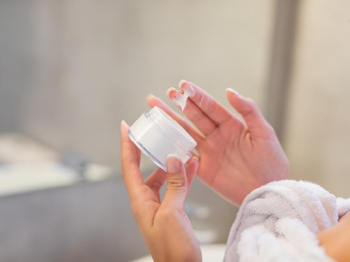 Hand holding a facial cream jar and taking cream out with fingers