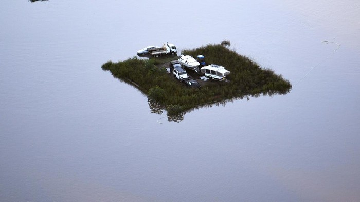 Equipment lies partly submerged at a property in Londonderry on the outskirts of Sydney, Australia, Tuesday, March 23, 2021. Hundreds of people have been rescued from floodwaters that have isolated dozens of towns in Australia's most populous state of New South Wales and forced thousands to evacuate their homes as record rain continues to inundate the countries east coast. (AP Photo/Mark Baker)