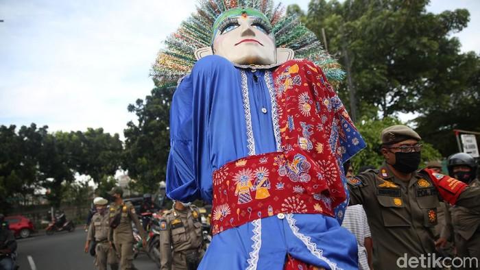 Petugas Satpol PP menangkap pengamen ondel-ondel di Buaran, Jakarta Timur, Rabu (24/3/2021).