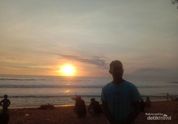 Pengunjung di Pantai Kuta sedang menikmati sunset.