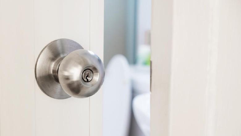 close up women twists doorknob to enter the bathroom
