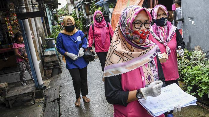 Sejumlah kader posyandu berjalan menuju rumah warga di Rorotan, Jakarta Utara.