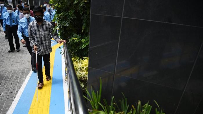 Penyandang tunanetra didampingi petugas berjalan di jalur pemandu di PN Jakarta Pusat, Jakarta, Kamis (25/3/2021). PN Jakarta Pusat memfasilitasi sarana dan prasarana bagi penyandang disabilitas untuk memberikan pelayanan peradilan kepada seluruh lapisan masyarakat. ANTARA FOTO/Hafidz Mubarak A/wsj.