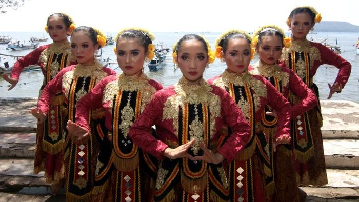 Penari menampilkan kreasi tari Larung Sesaji di tepi Pelabuham Satelit Muncar, Banyuwangi, Jawa Timur, Kamis (25/3/2021). Tarian yang ditampilkan oleh Padepokan Seni Dewi Sekartaji itu menceritakan nelayan muncar dalam melaksanakan tradisi petik laut sebagai warisan budaya leluhur. ANTARA FOTO/Budi Candra Setya/wsj.