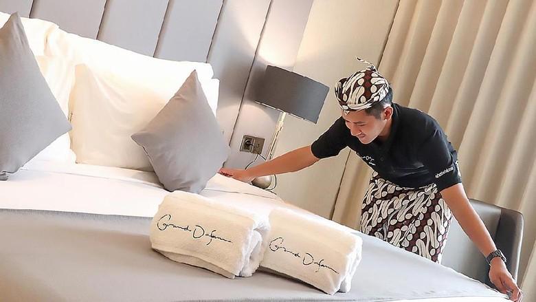 Karyawan Grand Dafam Signature membereskan kamar hotel di Surabaya.