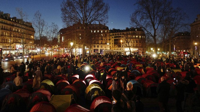 Migrants set up tents on the Republic square to draw attention to their living conditions and to demand accommodation, in Paris, Thursday, March 25, 2021. (AP Photo/Rafael Yaghobzadeh)