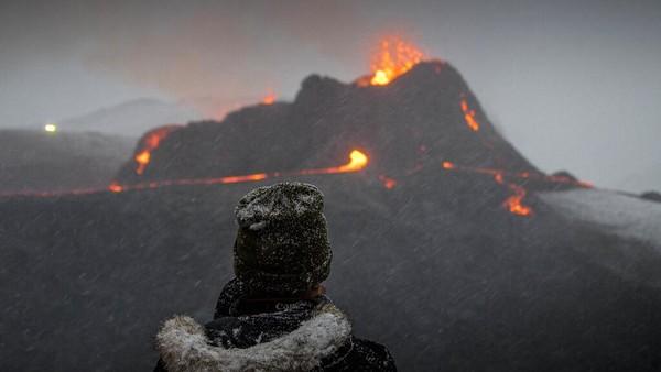 Seorang pengunjung menyaksikan erupsi gunung berapi Fahradaslfjall di lembah Geldigadalur, 40 km dari Reyjavik, Islandia.