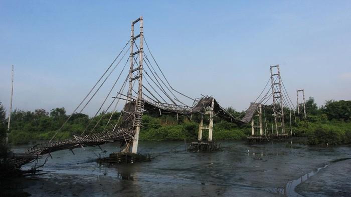 Warga melintas di dekat jembatan bambu di kawasan Ekowisata Mangrove Wonorejo, Surabaya, Jawa Timur, Sabtu (27/3/2021). Jembatan bambu yang dibangun pada tahun 2018 dengan panjang sekitar 600 meter dan tinggi sekitar 12 meter itu kondisinya rusak dan sudah tidak bisa dipergunakan lagi. ANTARA FOTO/Didik Suhartono/hp.