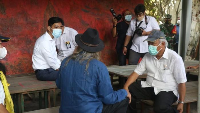 Walkot Solo Gibran Rakabuming Raka saat berdiskusi dengan Menteri PUPR Basuki Hadimuljono, Sabtu (27/3/2021). Foto ini disorot karena Gibran tampak duduk lebih tinggi dibandingkan Basuki yang lebih tua.
