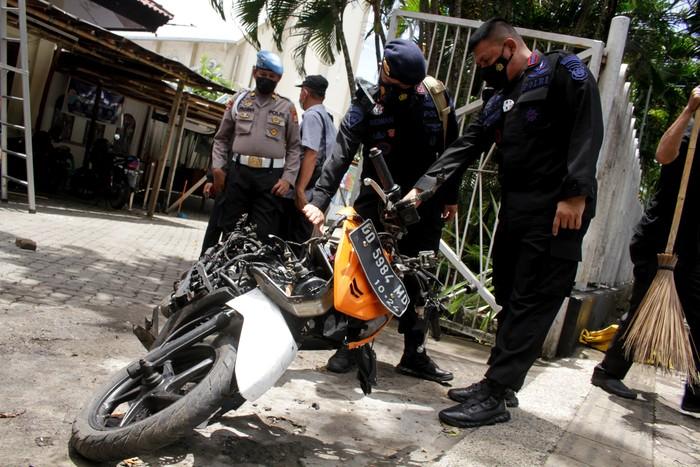 Anggota polisi mengamati motor yang digunakan terduga pelaku bom bunuh diri sebelum dievakuasi di depan Gereja Katedral Makassar, Sulawesi Selatan, Senin (29/3/2021). Kepolisian telah mengidentifikasi salah satu dari dua terduga pelaku bom bunuh diri yang terjadi pada Minggu (28/3/2021) di depan Gereja Katedral Makassa rberjenis kelamin laki-laki berinisial L sedangkan lainnya masih dalam proses identifikasi. ANTARA FOTO/Arnas Padda/yu/aww.