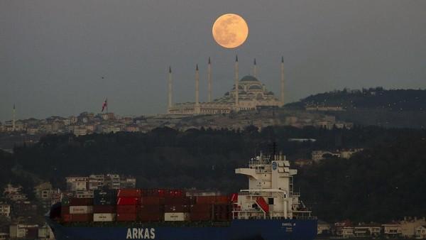 Bulan purnama terbit di atas langit di Istanbul, Minggu, 28 Maret 2021 dengan pemandangan Masjid Camlica, masjid terbesar di Asia Kecil.