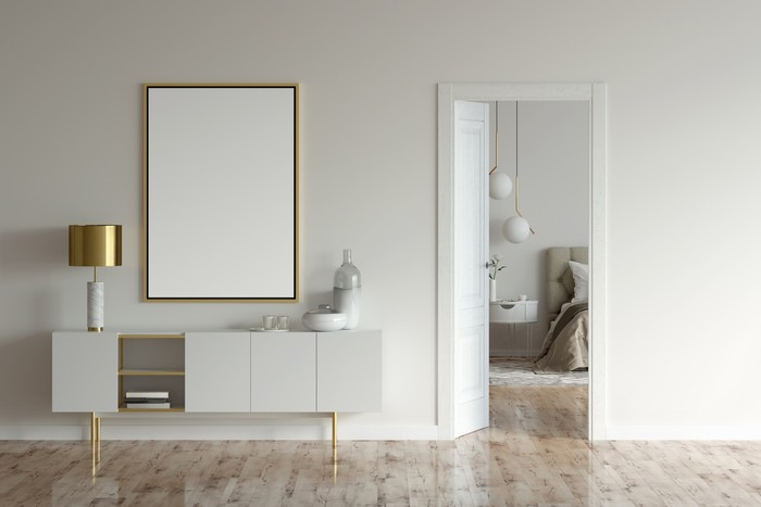 3d illustration. Mock up poster and a cabinet with lamp and decor in the beige interior with open door to the modern bedroom.