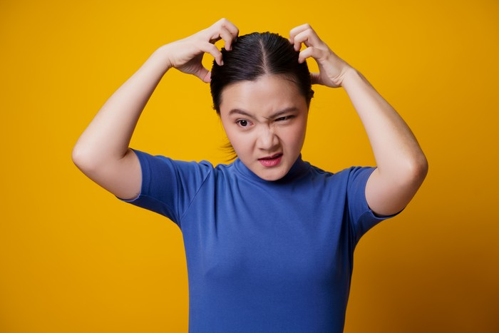Asian woman bored and annoyed, scratching her head, isolated on yellow background.