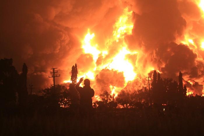 Warga mengambil video dengan gawai miliknya saat terjadi kebakaran di kompleks Pertamina RU VI Balongan, Indramayu, Jawa Barat, Senin (29/3/2021) dini hari. ANTARA FOTO/Dedhez Anggara/pras.