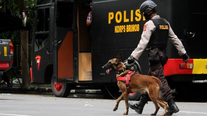 Anggota polisi berjalan dengan anjing pelacak saat mengumpulkan sisa serpihan ledakan bom bunuh diri di depan Gereja Katedral Makassar, Sulawesi Selatan, Senin (29/3/2021). Kepolisian masih melakukan olah TKP serta mengumpulkan serpihan sisa ledakan pada hari kedua pascaledakan bom bunuh diri yang terjadi pada Minggu (28/3/2021) di depan gereja tersebut. ANTARA FOTO/Arnas Padda/yu/aww.