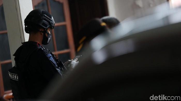 Polisi memasang garis polisi saat pengerebekan di Showroom Mobil Kemilau Motor, Condet, Jakarta, Senin (29/3/2021). Polisi menggerebek showroom mobil ini terkait terorisme.