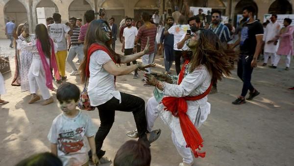 Warga menari diiringi musik selama merayaan Festival Holi. AP Photo/K.M. Chaudary