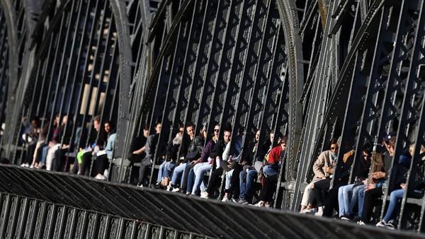 Kaum muda menikmati matahari terbenam di jembatan Hackerbrucke di Munich, Jerman.