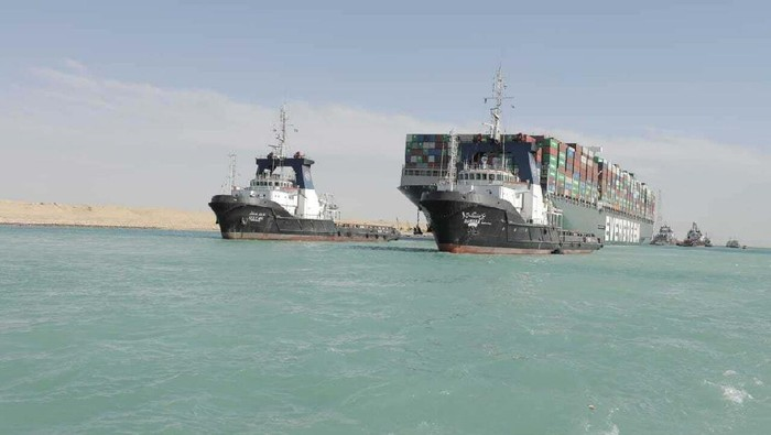 In this photo released by Suez Canal Authority, the Ever Given, a Panama-flagged cargo ship is accompanied by Suez Canal tugboats as it moves in the Suez Canal, Egypt, Monday, March 29, 2021. Salvage teams on Monday set free a colossal container ship that has halted global trade through the Suez Canal, bringing an end to a crisis that for nearly a week had clogged one of the worlds most vital maritime arteries. (Suez Canal Authority via AP)