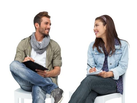 Full length of a cool young couple writing in notepads over white background