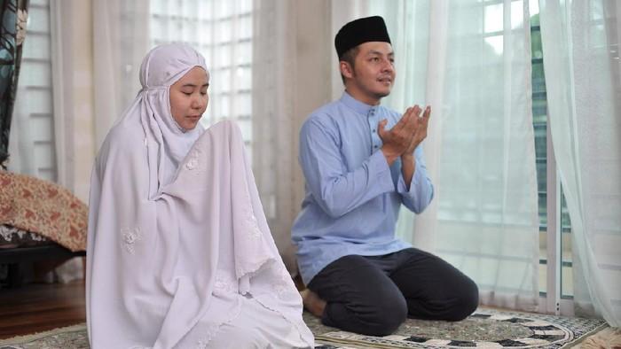 Asian family praying together during ramadhan