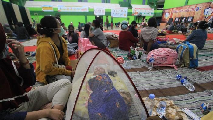 Menteri Sosial Tri Rismaharini (tengah) didampingi Bupati Indramayu Nina Agustina (kiri) melihat kondisi pengungsi yang terdampak kebakaran kilang Pertamina Balongan di Gedung Olahraga Bumi Patra Indramayu, Jawa Barat, Senin (29/3/2021) malam. Mensos tiba untuk memastikan kebutuhan dasar warga terdampak kebakaran yang berada di tempat pengungsian tetap terpenuhi dan terlayani dengan baik. ANTARA FOTO/Dedhez Anggara/rwa.
