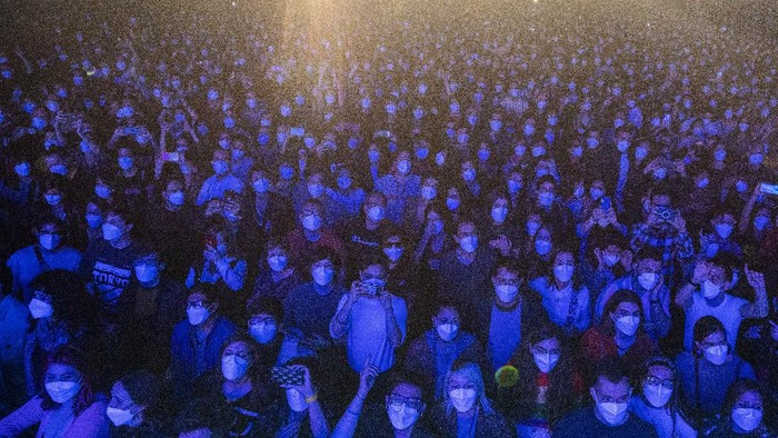 People take part in a music concert in Barcelona, Spain, Saturday, March 27, 2021. Five thousand music lovers are set to attend a rock concert in Barcelona on Saturday after passing a same-day COVID-19 screening to test its effectiveness in preventing outbreaks of the virus at large cultural events. The show by Spanish rock group Love of Lesbian has the special permission of Spanish health authorities. While the rest of the country is limited to gatherings of no more than four people in closed spaces, the concertgoers will be able to mix freely while wearing face masks. (AP Photo/Emilio Morenatti)