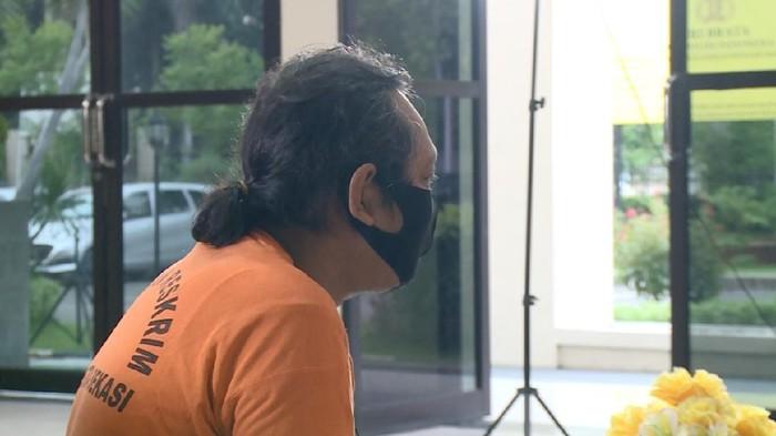 Herman alias Hermawan alias Ustaz Gondrong tersangka penipuan penggandaan uang. Foto diambil dari kamera reporter dan juga 20detik