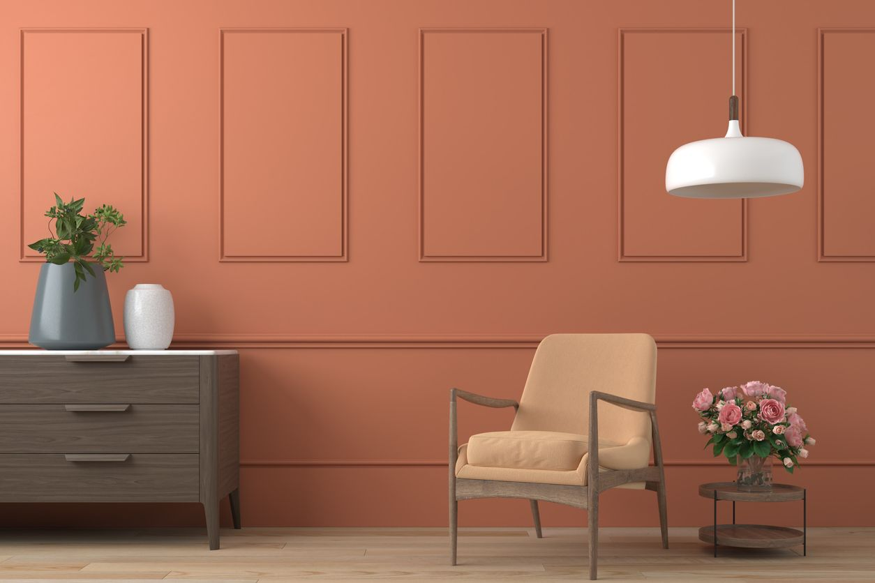 vibrant orange interior design background with peach colored armchair, lamp and cofee table with roses on modern moulding wall, 3d render