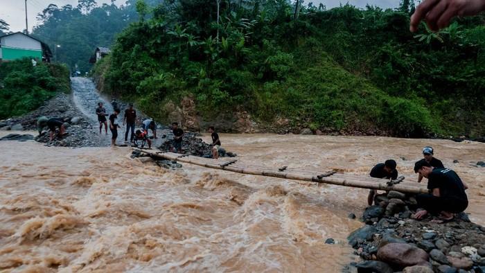 Warga secara swadaya membangun kembali jembatan di Desa Ciladaheun, Lebak, Banten, Selasa (30/3/2021).  Menurut keterangan warga setempat, setahun pasca diterjang bencana banjir bandang jembatan yang merupakan akses jalan nasional tersebut belum dibangun dan tidak bisa dilalui kendaraan ketika hujan deras karena air sungai Ciberang meluap. ANTARA FOTO/Muhammad Bagus Khoirunas/aww.