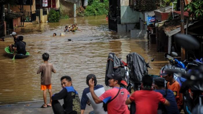Warga menggunakan perahu melintasi banjir yang menggenangi permukiman di Andir, Baleendah, Kabupaten Bandung, Jawa Barat, Kamis (1/4/2021). Ratusan rumah di Kecamatan Dayeuhkolot dan Baleendah terdampak banjir luapan Sungai Citarum setinggi satu hingga satu setengah meter akibat intensitas hujan yang tinggi di Bandung raya pada Rabu (31/3) sore hingga malam hari. ANTARA FOTO/Raisan Al Farisi/hp.