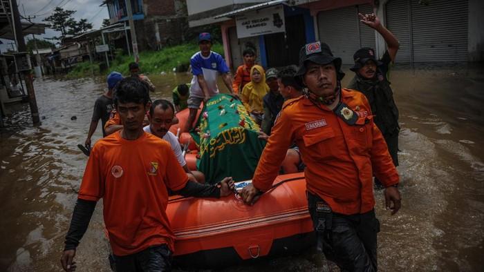 Petugas gabungan mengevakuasi jenazah menggunakan perahu karet di Andir, Baleendah, Kabupaten Bandung, Jawa Barat, Kamis (1/4/2021). Petugas gabungan dari BPBD, Pemadam Kebakaran, dan Tagana membantu mengevakuasi jenazah anggota keluarga yang meninggal dunia di permukiman yang terdampak banjir luapan Sungai Citarum. ANTARA FOTO/Raisan Al Farisi/foc.