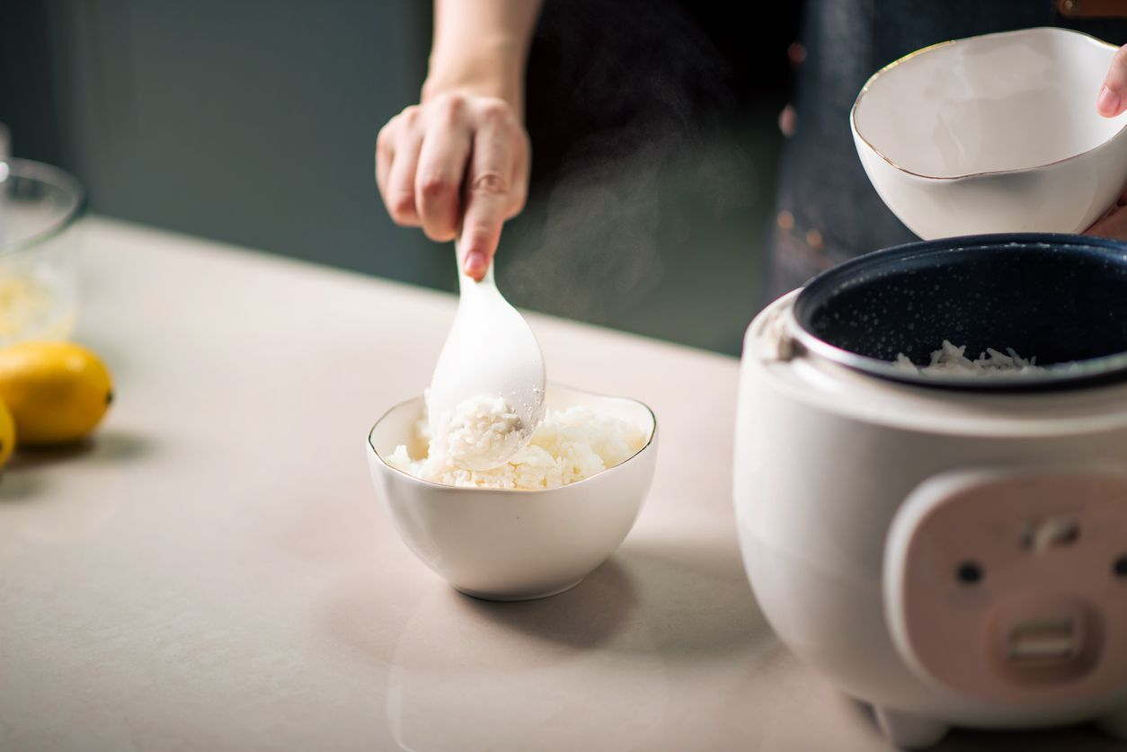 Woman taking out and serving fresh boiled fragrant jasmine rice from the rice cooker in the kitchen at home