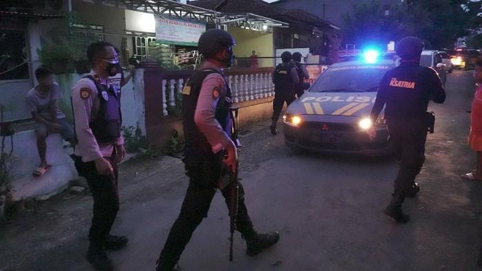 Polisi bersenjata melakukan penjagaan lokasi penggeledahan rumah terduga teroris oleh Densus 88 Anti Teror di Kelurahan Sumampir, Purwokerto, Banyumas, Jateng, Jumat (2/4/2021). Densus 88 Anti Teror dibantu Polresta Banyumas, melakukan penggeledahan rumah terduga teroris. ANTARA FOTO/Idhad Zakaria/hp.