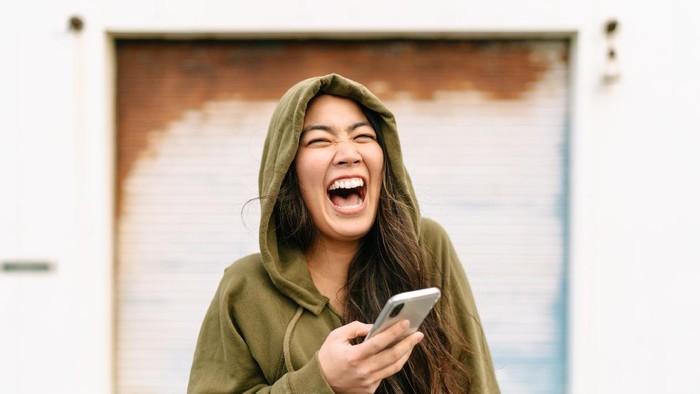 Ilustrasi wanita yang sedang tertawa ketika membaca pesan singkat.