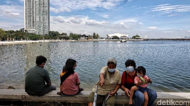 Sejumlah pengunjung menikmati Pantai Ancol, Jakarta Utara, Jumat (2/4).
