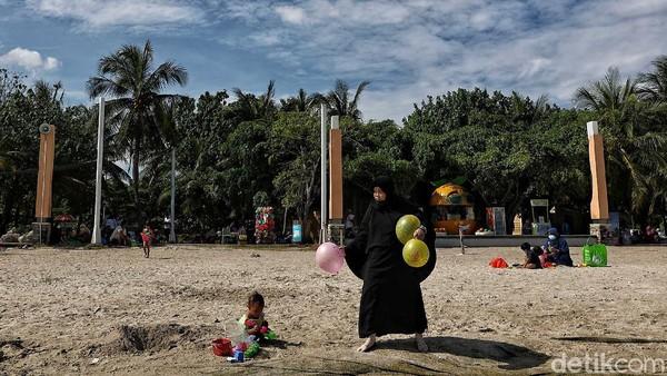 Seorang anak bermain pasir bersama orang tuanya.