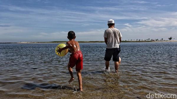 Seorang anak bermain di pantai bersama orang tuanya.